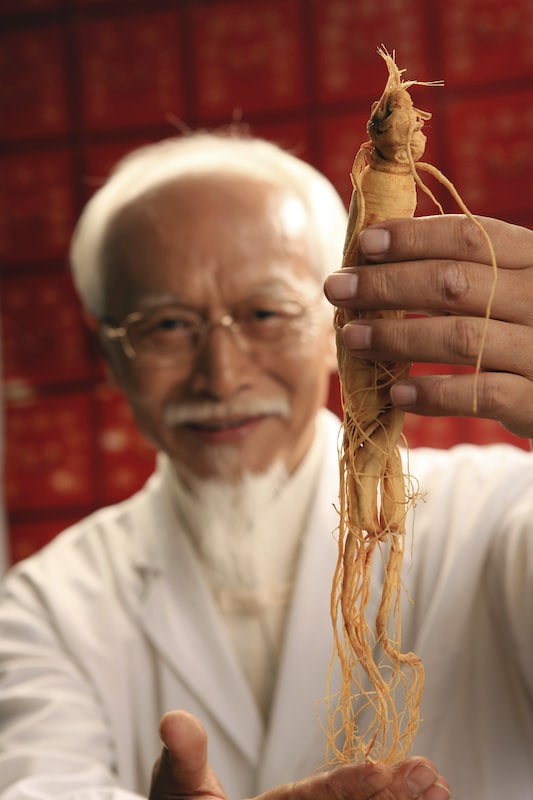 Chinese Doctor holding Ginseng